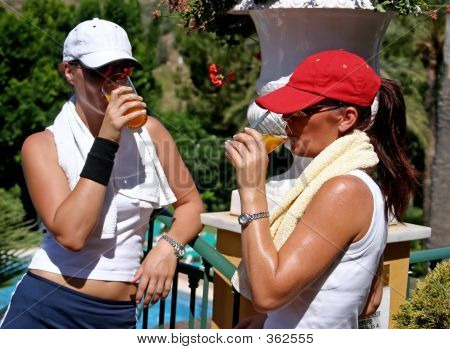 Two Young, Fit, Healthy, Tanned Women Having A Drink After A Hot Game Of Tennis