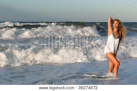 Woman In White Dress Posing On The Sea Coast