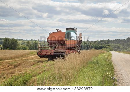Old harvester on the field near road