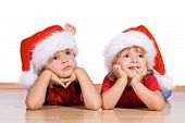 stock photo of gullible  - Boy and little girl dreaming about christmas - JPG