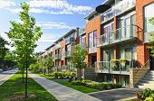 stock photo of public housing  - Modern town houses of brick and glass on urban street taken from public location  - JPG