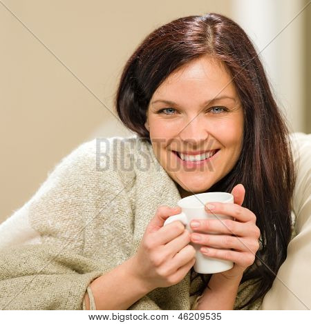 Portrait of joyful woman drinking hot beverage at home