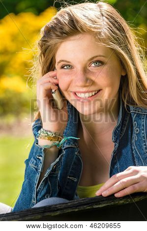 Joyful adolescent girl using her mobile phone in the park