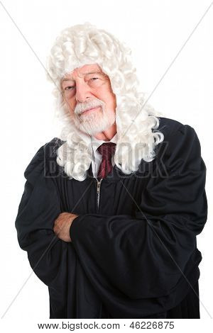 British style judge, in a wig, with his arms crossed and a skeptical expression.  Isolated.