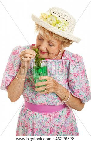 Senior lady getting a little bit drunk on a mint julep cocktail.  Isolated on white.
