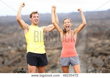 Cheering celebrating happy fitness runner couple with arms raised up in winning gesture expression outdoors on trail running path on Hawaii. Cheerful interracial couple, Asian woman, Caucasian man.