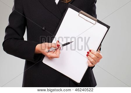 Pen on a blank paper in businesswoman hands with manicure