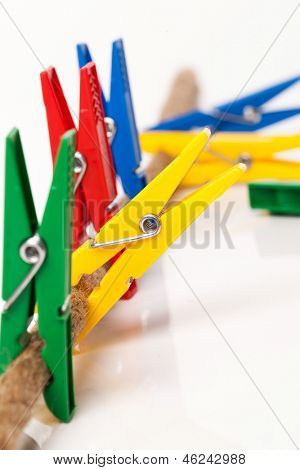 Closeup image of colorful clothespins with cord on a white background
