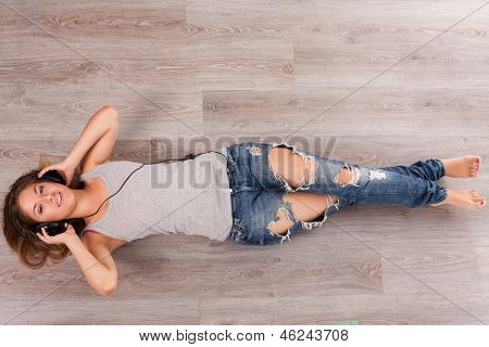 Beautiful caucasian woman listening music with headphones lying on the wooden floor