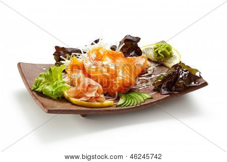 Salmon Sashimi - Sake (fresh raw salmon) on Daikon (White Radish). Garnished with Ginger, Wasabi, Seaweed, Cucumber, Salad Leaf and Lemon