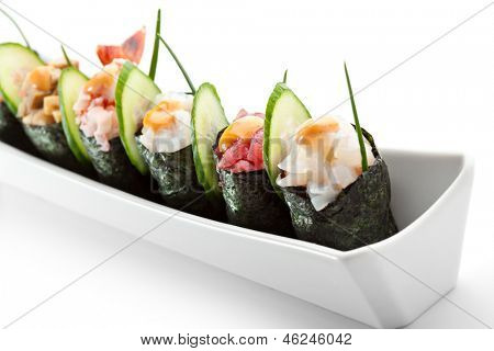 Würzige Gunkan Sushi - Lachs, Omelett, Garnelen, Tintenfisch, Thunfisch und Jakobsmuscheln. Garniert mit Gurke