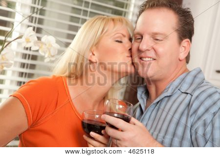 Kissing Couple Enjoying Wine Together