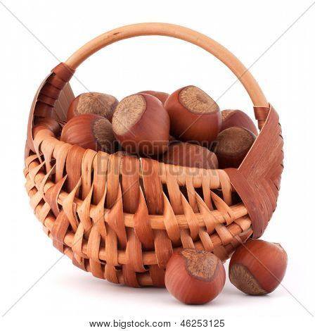 Hazelnuts in wicker basket isolated on white background