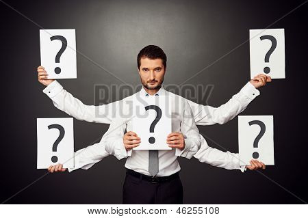 empresario serio con cinco manos sosteniendo pancartas con signos de interrogación