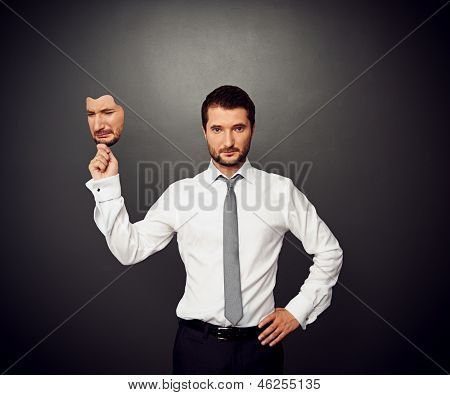 serious businessman holding mask with crying face