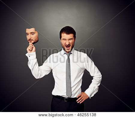 irate man holding mask with calm mood