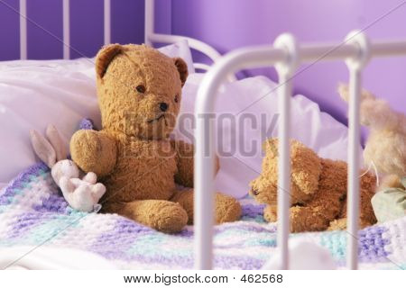 Scruffy Old Teddy Bears On A Child's Bed