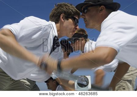 Closeup side view of sailors operating windlass on yacht against clear blue sky