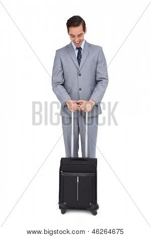 Smiling young businessman waiting with his suitcase on white background