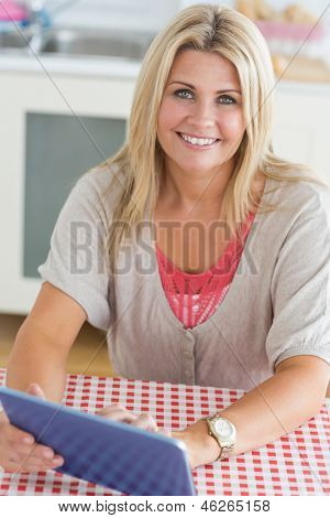 Smiling woman working on digital tablet at the kitchen table