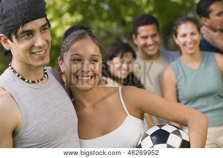 Young couple with woman holding soccer ball and family in the background