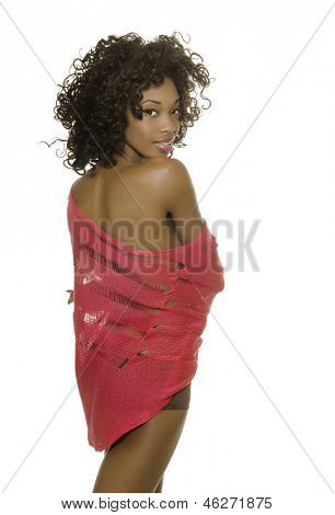 Beautiful African-American woman wearing pink knit shawl top and lingerie with bare shoulder looking back and smiling.