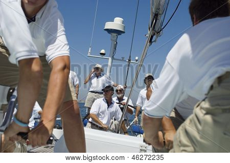 Portrait of a smiling sailor with crew on the sailboat deck against clear sky