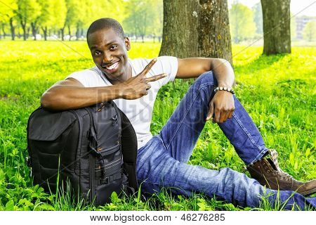 Young smiling african american man with rucksack in a park