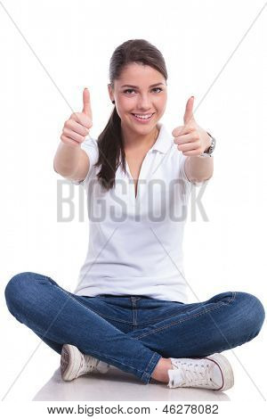 casual young woman sitting with legs crossed showing both thumbs up gesture. isolated on white background