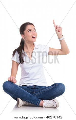 casual young woman sitting with legs crossed pointing and looking up while smiling. isolated on white background