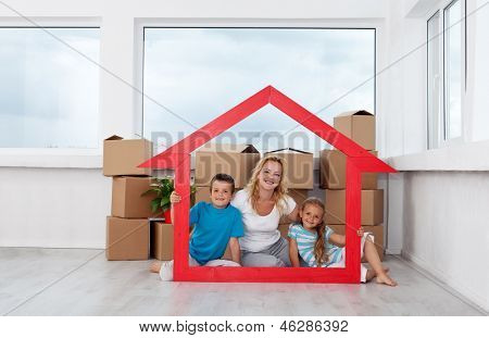 New home concept with woman and kids and lots of cardboard boxes in empty room
