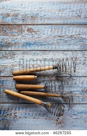 retro kitchen utensils whisks  on old wooden table in rustic style