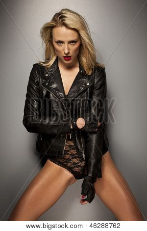 Seductive woman posing in a black leather jacket, gloves and lacy lingerie giving the camera a sultry look