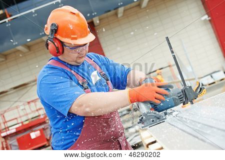 Builder worker with power tool circular saw machine cutting plastic parts at construction site