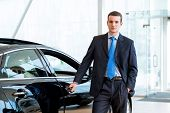 image of showrooms  - dealer stands near a new car in the showroom - JPG