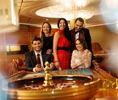 pic of roulette table  - Group of young people behind roulette table in a casino - JPG