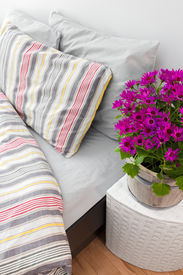 foto of pillowcase  - Bright purple flowers decorating a modern bedroom with striped bed linen - JPG