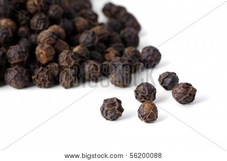 Detail shot of a pile of black peppercorns. All isolated on white background.