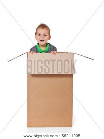 Attractive young boy inside moving box. All on white background.