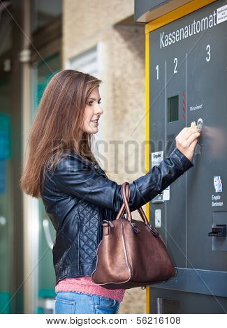 Attractive young woman using the parking ticket vending machine