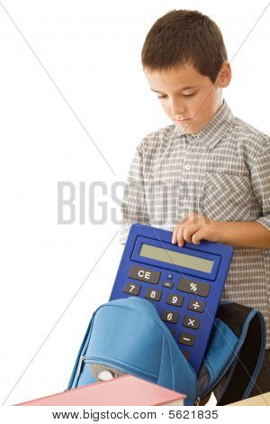 Schoolboy Putting A Calculator In The Schoolbag
