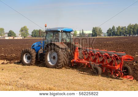 agriculture tractor with plough in field