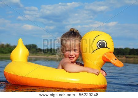 little girl bathes in summer river in inflatable duck