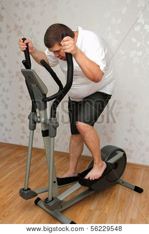 overweight man exercising on trainer ellipsoid