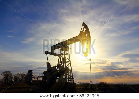 working oil pump at sunset with sunbeams