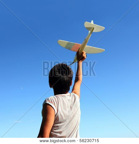 happy boy running airplane model under blue sky