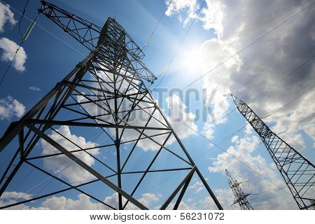 tall electric masts against sun and cloudy sky