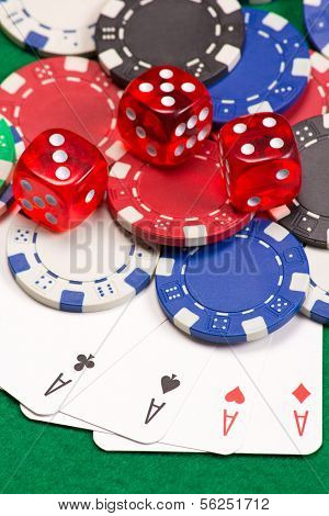 Poker Chips, Dice And Four Aces On The Green Table