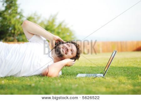 Happy Young Man On Green Meadow With Laptop