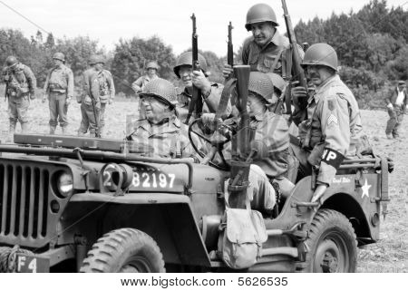 World War II re-enactors riding in a jeep